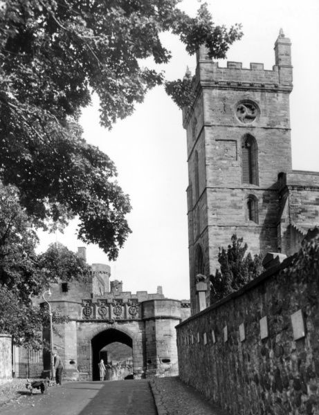 The fine outer gateway to Linlithgow Palace, West Lothian, Scotland, built for King James V in 1535. On the right is the tower of St. Michael's Church. Date: early 16th century