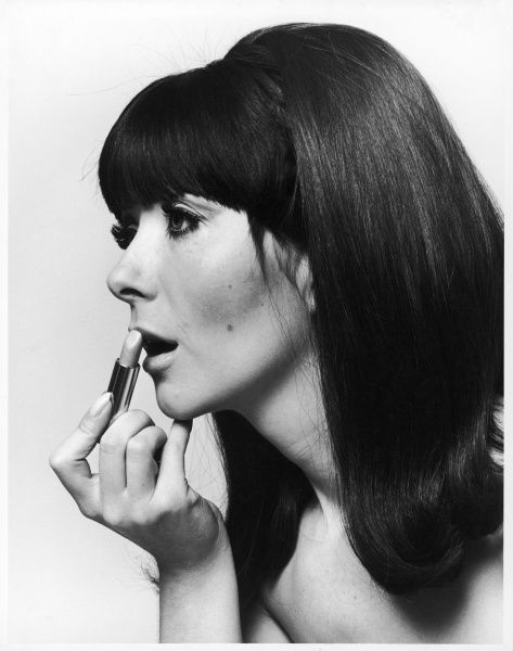Girl with thick dark hair cut into a fashionable hairstyle with a fringe, applying pale lipstick