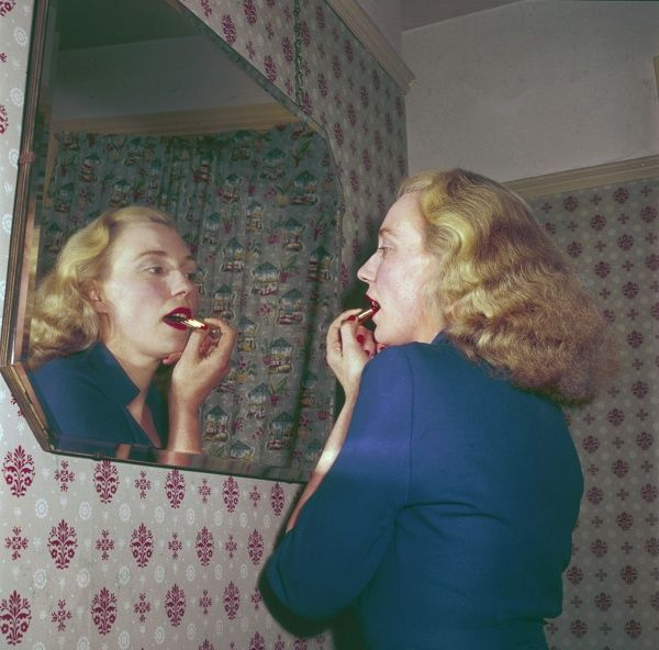 A strawberry blonde looks in the mirror, putting the finishing touches to her lipstick before going out on the town