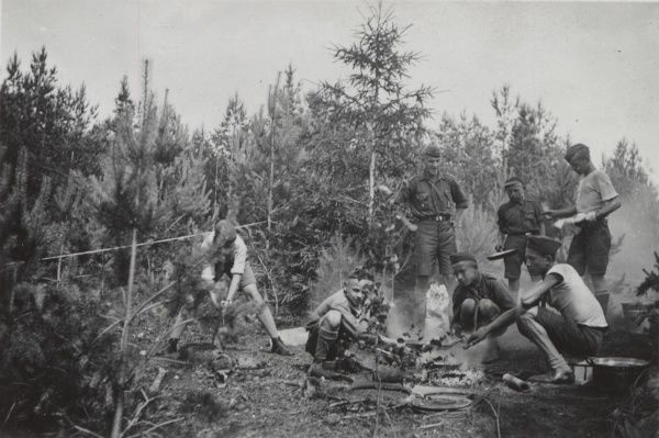 A group of Lithuanian Boy Scouts stop during a hike in a coniferous forest to cook some food by chopping down trees and making a small fire. circa 1951