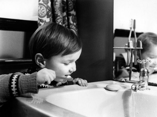 A little boy brushes his teeth -- he can only just reach over the washbasin. (1 of 2)