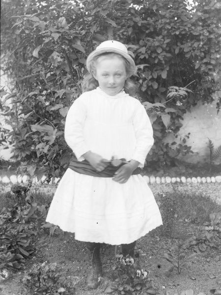 A little Edwardian girl in a white dress and dark sash poses in a garden, Mid Wales