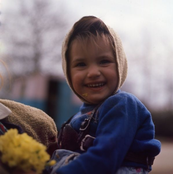 A little gipsy girl, member of the Vincent family, in the Newdigate area of Charlwood, Surrey. She is wearing bright blue clothes and a cream-coloured headscarf, and is holding a bunch of yellow flowers