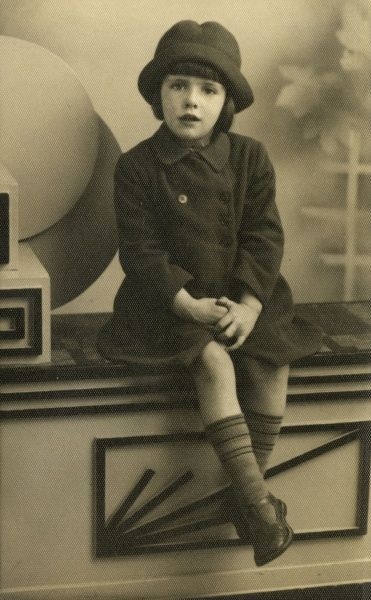 A little girl poses for her photograph in an Art Deco style studio. Date: 1930s