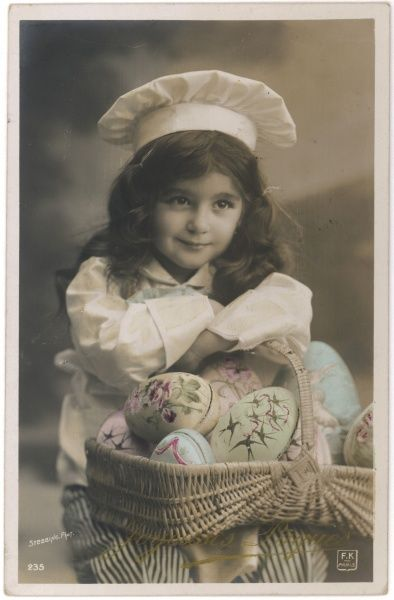 A sweet little girl with a nice smile, wearing a chef's costume and carrying a basket full of large painted eggs