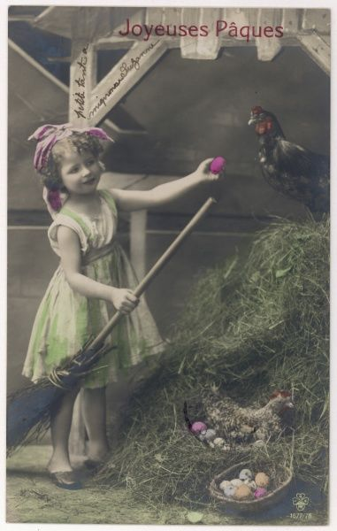 A little girl collecting eggs in a poultry yard fills her basket with coloured eggs