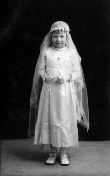 A little girl dressed all in white for her (Roman Catholic) confirmation. Date: circa 1930s