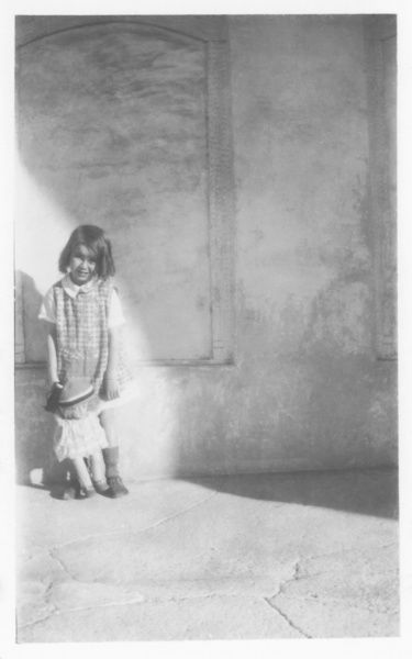 A little European girl poses with her doll, in a mixture of sunlight and shadow, somewhere in the Middle East