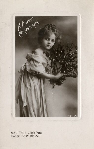 A pretty little girl on a Happy Christmas postcard, with the inscription: Wait Till I Catch You Under The Mistletoe.  circa 1916