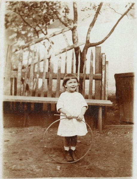 A little girl in a garden or back yard with her hoop and stick, a popular game at the time. She is from the settlement of Kostel (also known as Podivin) in South Moravia, now in Czechoslovakia