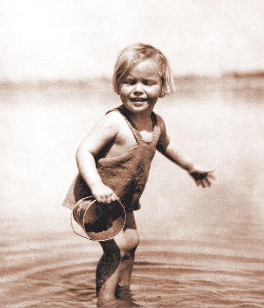 A little girl paddling, with a bucket in her hand. She is wearing a knitted swimsuit