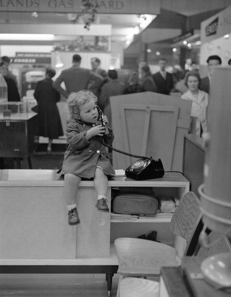 A little girl on the telephone seated on the desk of a stand at a Trade Show. The 'Midlands Gas Board' stand can be seen in the background. Photograph by Norman Synge Waller Budd