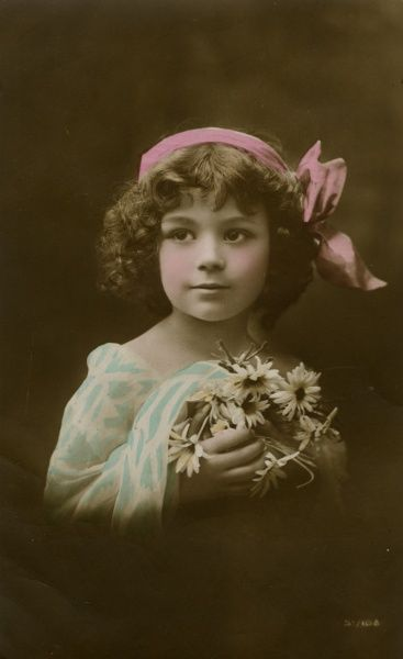 A little girl in pink, blue and white, holding some flowers.  1918