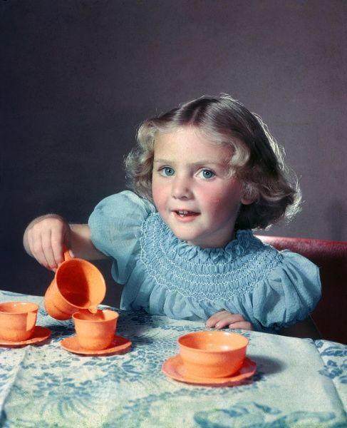 A pretty young girl pouring herself a cup of pretend tea using a bright orange plastic tea set. Photograph by Heinz Zinram