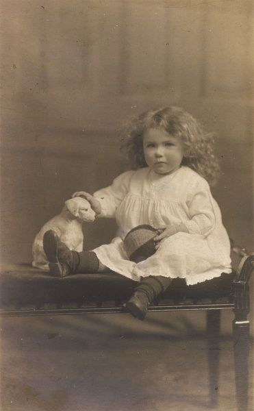 A little, curly haired girl poses with a ball and an ornament in the shape of a dog