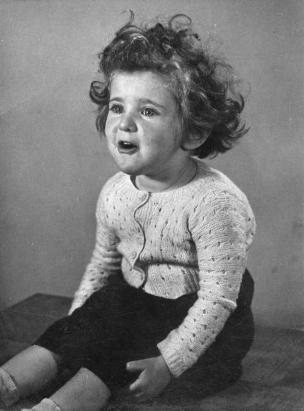 A little girl who appears to be on the verge of tears. She is sitting on a table top, wearing a knitted cardigan and a dark skirt