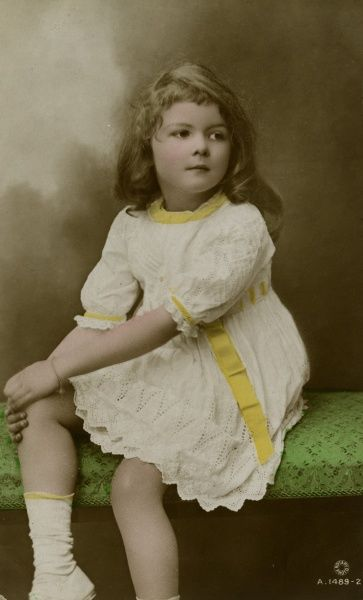 A little girl in a frilly white dress with yellow trimmings. Date: early 20th century