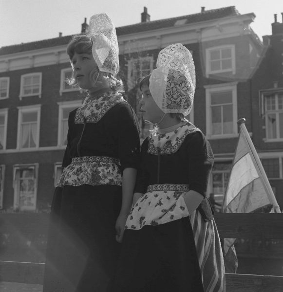Two little girls in Belgian national costume, including delicate lace bonnets