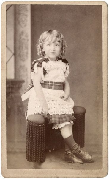 A little Victorian girl poses in the photographer's studio, wearing a white lacy dress with tartan trimmings. Her blonde hair is in ringlets