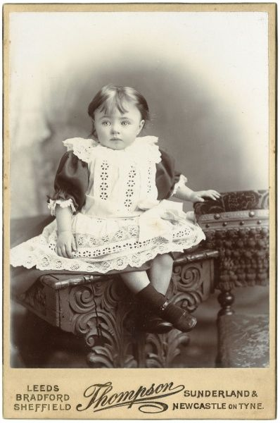 A sweet little Victorian girl poses in the photographer's studio, wearing a white lacy dress. She is sitting on an ornately carved wooden table, and resting her hand on the back of a chair