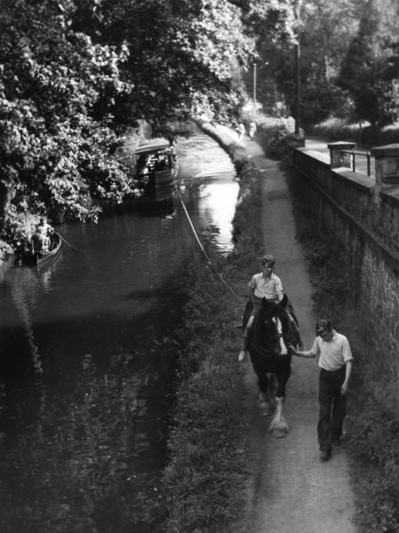 A boy on a horse pulling along a pleasure boat on the tow path of the Llangollen Canal, Denbighshire, Wales. Date: early 1960s