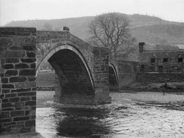 An imposing view of the elegant stone bridge which spans the River Conwy at Llanwrst, Wales. Date: 17th century
