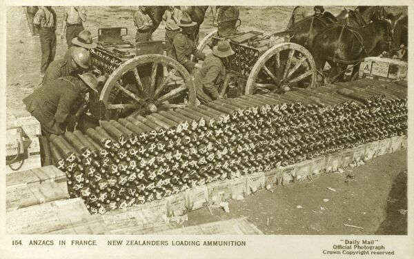 Loading artillery shells - Anzac New Zealand soldiers in active service in France during World War One. The postcard shows the artillery shells being packed into their limbers from a large open-air dump, ready for the firing line. Date: circa 1916