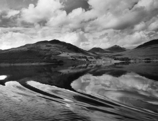 A loch steamer's bow wave in the still waters of Loch Katrine, the Trossachs, Perthshire, Scotland. The hills round Strath Gartney are in the background. Date: 1950s