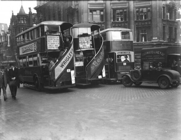 Three London buses, with steps at the back to enable passengers to hop on and off with ease