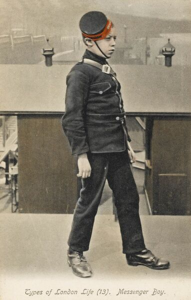 London Messenger Boy in traditional uniform, with cap (at a jaunty angle) standing on a pier on the Thames