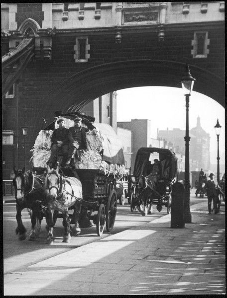 A rag and bone horse and cart and other horse drawn vehicles, about to cross Tower Bridge, London, England