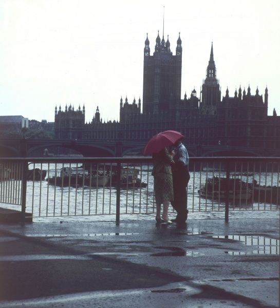 A couple shelter from the rain under a red umbrella during a romantic walk beside the River Thames and the Houses of Parliament, Westminster, central London. Date: 1960s