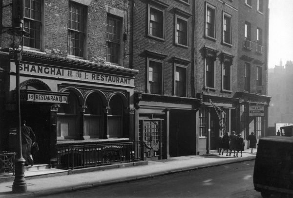 A London street scene, featuring the Shanghai Restaurant, and a shop to let on the corner.  circa 1940s