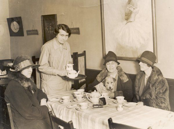 Three ladies in fashionable cloche hats, one with her dog on her lap,enjoy tea and cake at a London teashop next door to Wyndham's Theatre