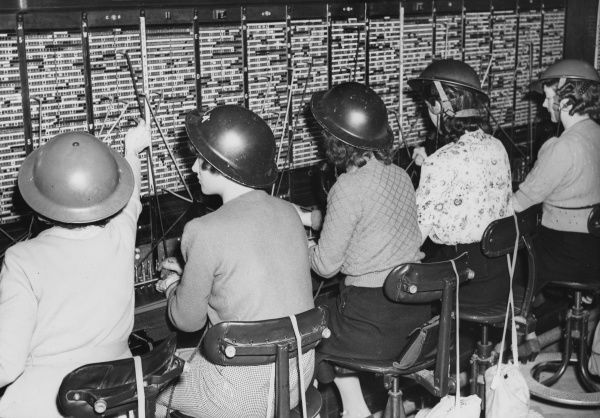 Women telephone operators at a London telephone exchange with tin helmets, during World War II