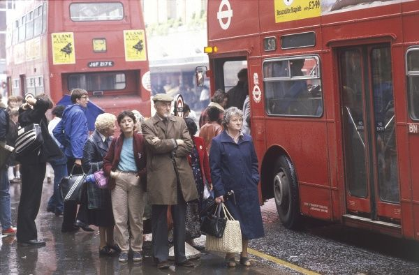 A miserable scene at a London bus stop, commuters nearly fighting to get onto buses, perhaps during a tube strike. Date: 1980s