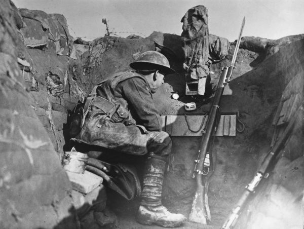 A soldier in a look-out post in a trench using a camouflaged periscope to keep watch on the British Front in France during World War I in 1917. He has a short magazine Lee Enfield Mk III rifle beside him. Date: 1917