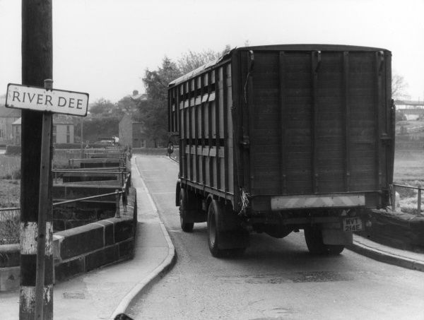 A lorry going over the narrow Farndon Bridge over the River Dee, Cheshire, England. Date: 1960s
