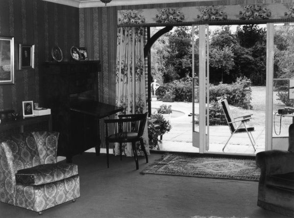 A 'modern' lounge, with doors which open to the garden patio and lead (of course) to the pool. Date: 1970s