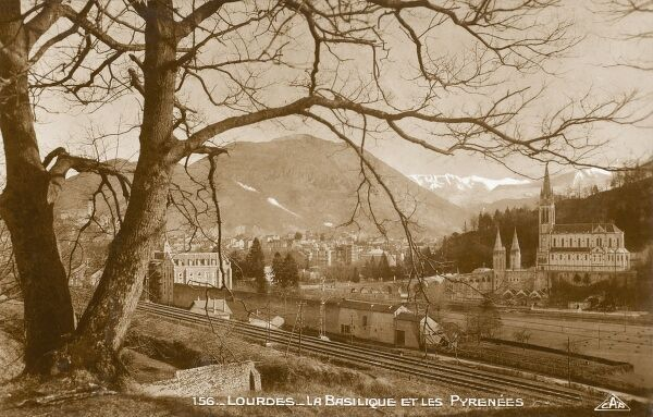 A panoramic view of Lourdes, France, showing the Rosary Basilica of the Sanctuary of our Lady at Lourdes and the distant mountains of the Pyrenees
