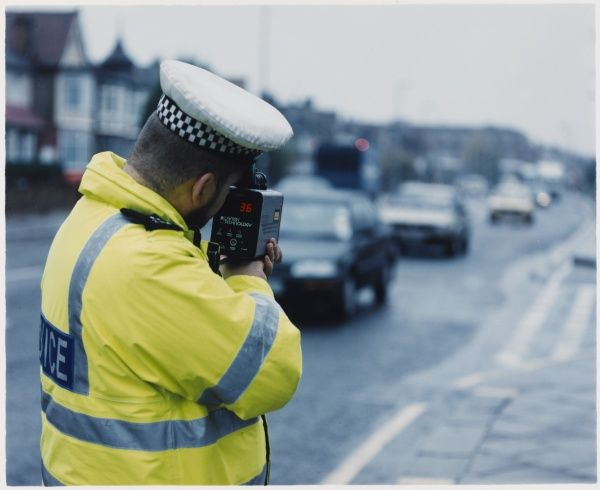 Metropolitan police officer with LTI 20-20 speed gun checking the speed of cars in the traffic