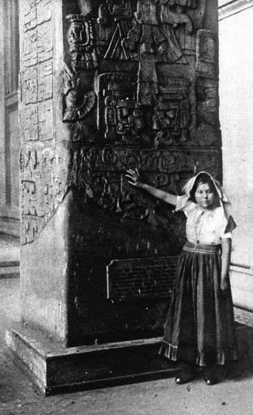 Believed to be the first of a dying race of Maya indians who has ever visited England: Emilia Vasquez standing by an ancient Maya monolith in the British Museum, where she was introduced to a lecture audience by explorer Mr