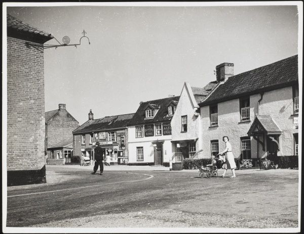 A woman pushes a pram through the pretty village of Ludham in Norfolk