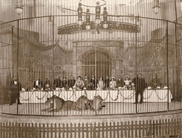 An unusual luncheon party which took place at the Imperial International Exhibition in Shepherds Bush (White City). Twenty people in a large cage with four full-grown lions belonging to Bostock's Circus are about to sit down for their lunch