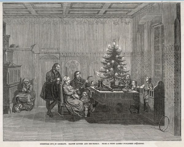German religious reformer Martin Luther and his wife Katharina von Bora sit with their family round the Christmas tree