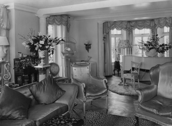 An eye-catching living room, with a stylish satin suite, ruched curtains, parque flooring, Romanesque columns, flower arrangements, a baby grand piano, leopardskin rug