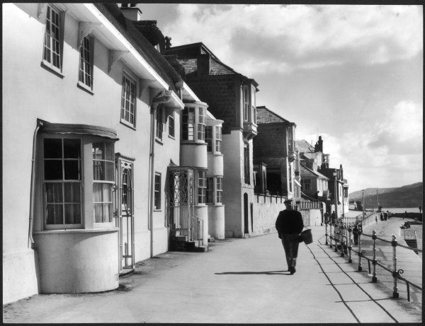 An old man with a bucket over his arm walks along the sea front at Lyme Regis, Dorset, England