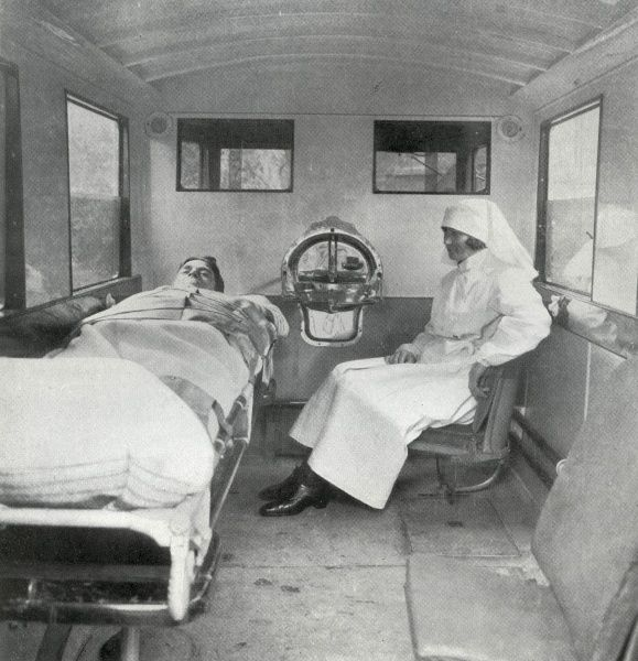 Interior of one of the ambulances operated by London's Metropolitan Asylums Board in around 1930, showing a patient lying on a bed and a nurse sitting at his side