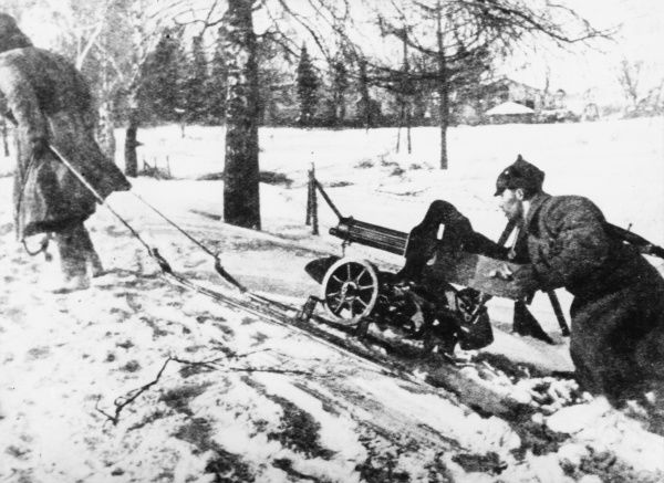 Two soldiers moving a machine gun into position during World War II in Finland