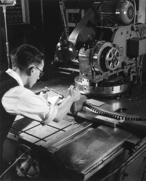 A smart young worker, wearing spectacles and a waistcoat, operating a machine tool presss. Date: 1950s
